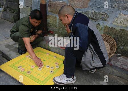 Two men playing  Chinese chess at Fenghuang , Hunan China - Stock Photo