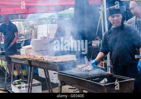Cooking pork kebabs on a barbecue. - Stock Photo