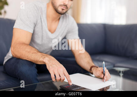 Young casual man calculating on desk, black paper and calculator - Stock Photo