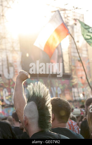 Man with punk hair style and polish flag during concert on the 21th Woodstock Festival. - Stock Photo