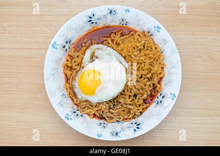 Korean noodles(Ramen) in flower bowl on wooden table. - Stock Photo