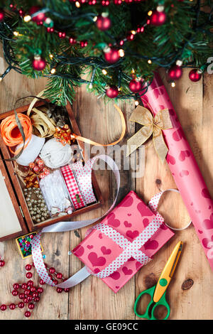 Wrapping and decorating Christmas gifts with colourful paper and ribbons - Stock Photo