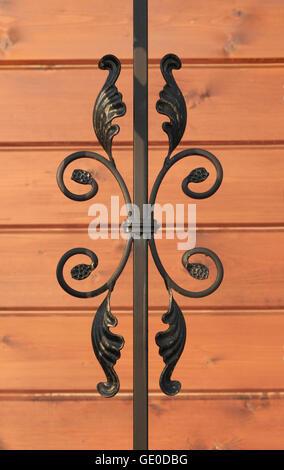 Wrought-iron fence elements of railing on wooden background photo - Stock Photo