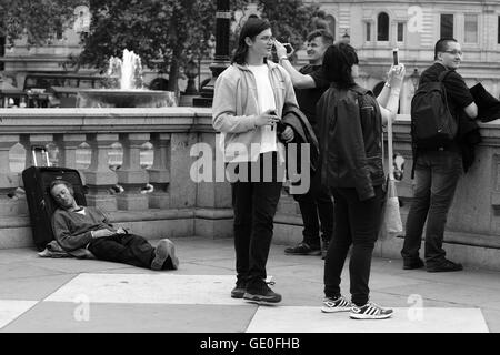 A mle lies on the ground in Trafalgar Square, sleeping, while tourists stand nearby looking at and taking photographs - Stock Photo
