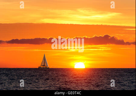 Sailing sunset is a sailboat moving along the water as the sun is going down on the ocean horizon. - Stock Photo