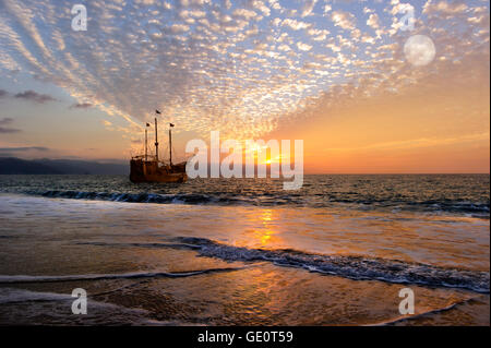 Pirate ship moon is an old antique ship out at sea with full flags flying as the sun sets on the ocean horizon and - Stock Photo