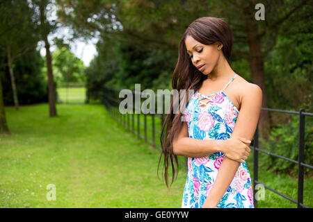 thoughtful woman in a summer dress outdoors. - Stock Photo