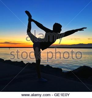 Silhouette of girl doing standing bow pulling pose by beach, California, America, USA - Stock Photo
