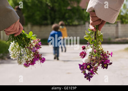 Two women and two boys going for a walk holding flowers - Stock Photo