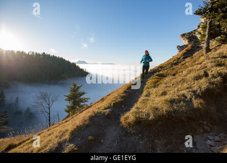 Woman Trail Running in the Mountains above the Clouds, Salzburg, Austria - Stock Photo