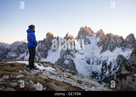 Woman standing in the Dolomite Mountains looking at view, South Tyrol, Italy - Stock Photo