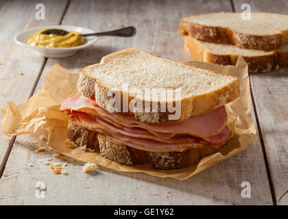 A smoked meat sandwich on a wooden table with mustard. - Stock Photo