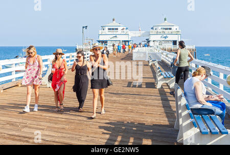 Malibu, USA - August 23, 2015: People walking on the Malibu Pier, reopened in June 2008 after serious renovations. - Stock Photo