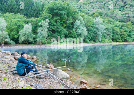 Fishing adventures, carp fishing. Fisherman on the banks of a lake - Stock Photo