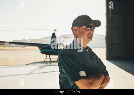 Portrait of helicopter pilot in uniform standing with his arms crossed and looking away with a helicopter in background - Stock Photo