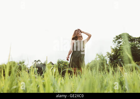Portrait of beautiful young woman standing outdoors. Female fashion model posing outdoors. - Stock Photo