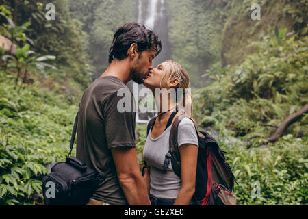 Shot of loving young couple kissing while standing in the forest. Couple in love kissing near a waterfall in forest. - Stock Photo