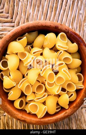 Uncooked Conchiglie pasta shells in a bowl - Stock Photo