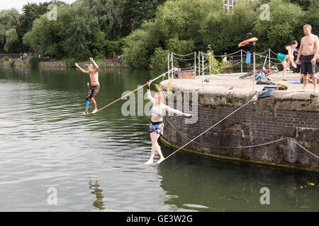 Shadwell, London. UK. 23rd July 2016. People enjoying slacklining during hot sunny weather at Shadwell Basin in - Stock Photo