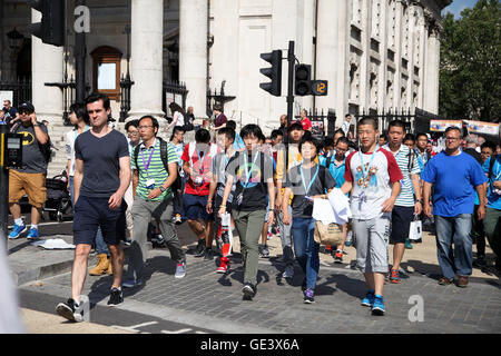 London, UK. 23rd July, 2016. Group of tourist crossing the road as the temperatures reaches to 27 degrees celsius - Stock Photo