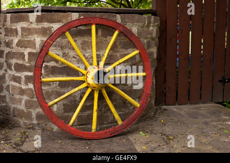 old wagon wheel with metal rim leaning on a stone wall - Stock Photo