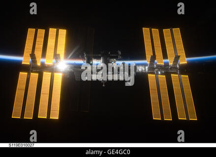 Backdropped by the blackness of space and the thin line of Earth's atmosphere, the International Space Station is - Stock Photo