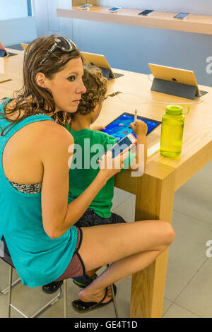 A mother sits with her son while he plays with an iPad and she holds her iPhone at the Apple Store in Santa Barbara, - Stock Photo