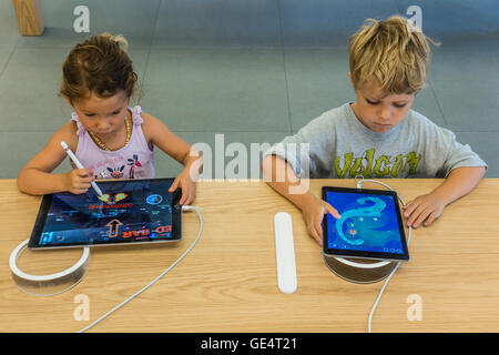 Two children, 6-8 years old try out iPads at the Apple Store on State Street in Santa Barbara, California. - Stock Photo