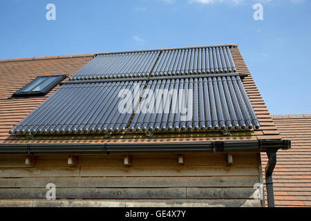 Array 80 solar thermal tubes barn roof Cotswolds UK - Stock Photo