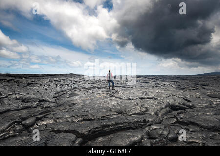 Hiker standing over amazing formation of magma on lava field in Hawaii Volcanoes National Park - Stock Photo