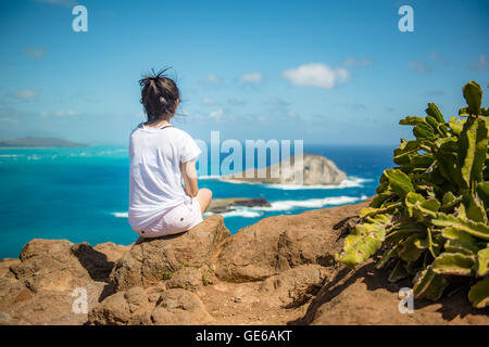 Asian girl relaxing and watching fabulous top view of Big Island on the cliff, Hawaii USA - Stock Photo