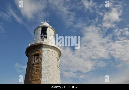 Woodman Point Lighthouse with it's limestone brick exterior half painted white with a cloudy sky in Coogee, Western - Stock Photo