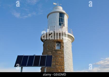 Woodman Point Lighthouse with half-painted white limestone brick exterior and solar panel under a blue sky in Western - Stock Photo