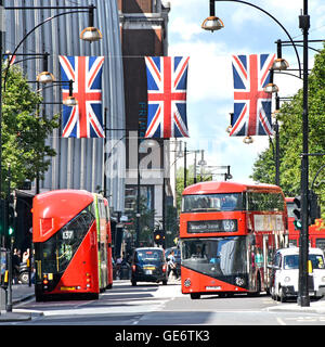 Oxford Street West End London England UK new red double decker Routemaster buses below Union Jack flags in this - Stock Photo