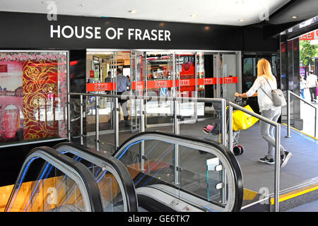Doorway to ground floor entrance of Oxford Street branch of House of Fraser department store with escalators to - Stock Photo