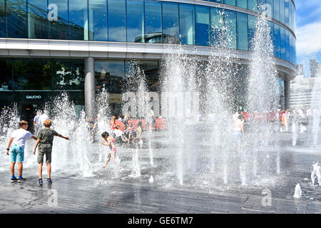 Water jets rising above block paving at random timings during hot London UK summer weather as office workers take - Stock Photo