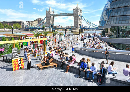 Hot day for office workers & tourists at summertime drinks & food stalls around 'The Scoop' beside London uk City - Stock Photo