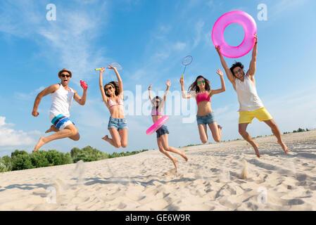 Positive friends having fun on the beach - Stock Photo