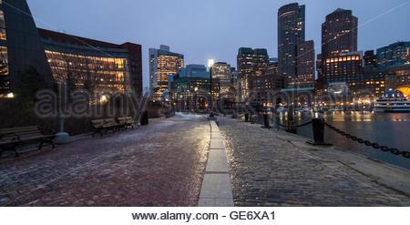 Slick layer of ice glistens under lights before dawn along Boston Harborwalk - Stock Photo
