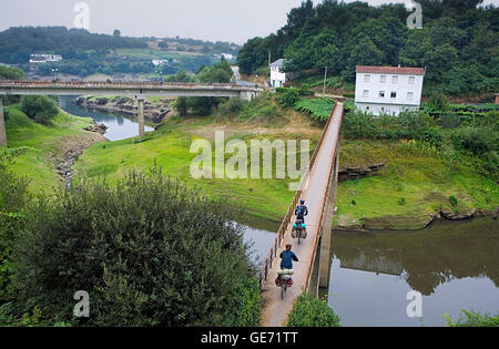 Pilgrims on bike throught the bridge to go out of Portomarín. Arroyo Torres. Portomarín. Lugo  province.Spain. Camino - Stock Photo