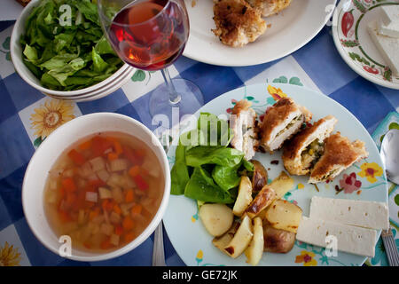 Chicken kiev, vegetable soup, green lettuce salad and glass of red wine adorn a kitchen table dressed in traditional - Stock Photo