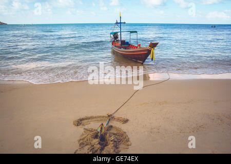 A boat is anchored at Bottle Beach, Koh Pha Ngan, Thailand - Stock Photo