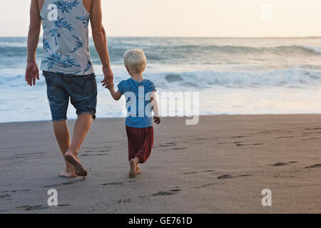 Happy family - barefoot father holds baby son hand, walk with fun along sunset sea surf on black sand beach. Travel - Stock Photo