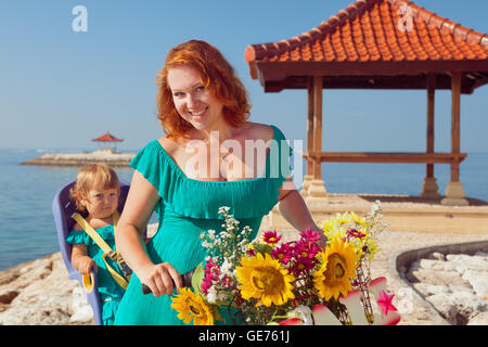 Happy family - mother bicycling and have fun with little daughter in baby bike seat on sea beach. Active parents, - Stock Photo