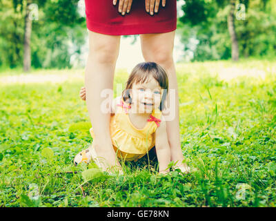 one-year old baby girl between mother legs outdoors - Stock Photo