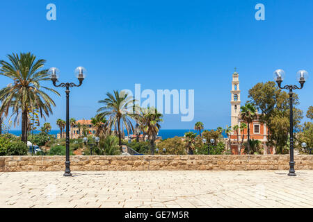 Saint Peter's church among palms under blue sky as seen from view point with lampposts in Jaffa, Israel. - Stock Photo