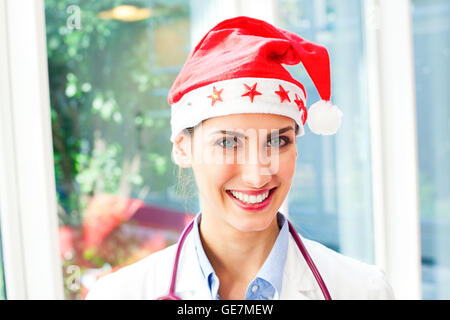 Portrait of happy female doctor wearing Santa hat. Beautiful young medical professional is smiling. She is with - Stock Photo
