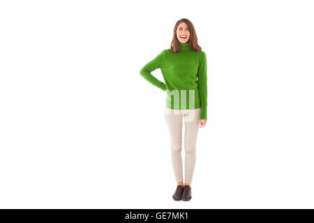 Full length of young woman smiling. Beautiful female is wearing green turtleneck sweater. She is standing isolated - Stock Photo