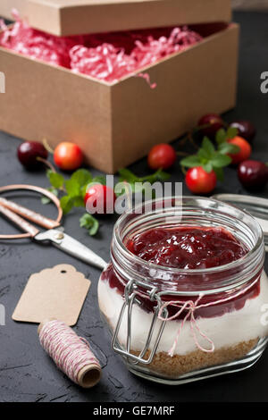 homemade gift is not baking cheesecake with cherries in a glass jar - Stock Photo