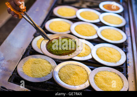 Chef cooking traditional Turkish delicious dessert Kunefe and show cooked Kunefe with pistachio powder closeup - Stock Photo
